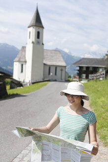 Austria, Young woman holding hiking map, smiling - FLF000344