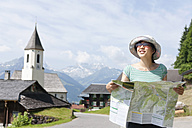 Austria, Young woman holding hiking map, smiling - FLF000345