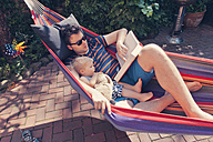 Germany, Bonn, father and little son looking at a book while in hammock - MF000612