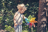 Germany, Bonn, Little boy spinning a colorful wheel in garden - MF000604