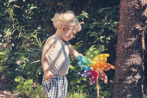 Germany, Bonn, Little boy spinning a colorful wheel in garden - MF000604