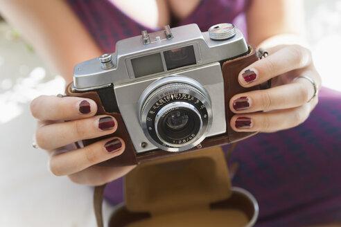 Germany, Bavaria, Munich, Young woman holding camera, close up - TCF003510