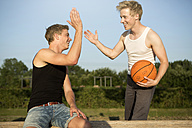 Germany, Two young men meeting up to play basketball - GDF000141