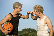 Germany, Two young man meeting up to play basketball - GDF000143
