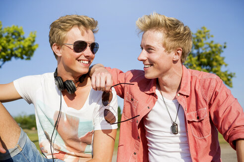 Germany, two friends listening to music with headphones - GDF000158