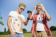 Germany, Young men checking their looks in smart phone - GDF000159