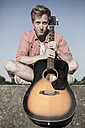 Germany, Young man sitting on wall with guitar - GDF000180