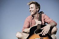 Germany, Young man holding guitar, looking away - GDF000182