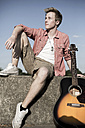 Germany, Young man sitting on wall with guitar - GDF000185