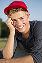 Germany, Young man in park, smiling - GDF000198