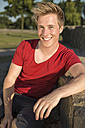 Germany, Young man sitting in park, smiling - GDF000193