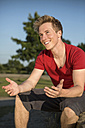 Germany, Young man sitting in park, gesturing - GDF000188