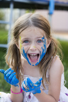 Germany, Bavaria, Portrait of girl playing with finger paint, smiling - SARF000086