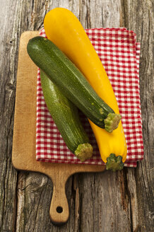 Green and yellow courgettes with napkin on chopping board, close up - OD000273