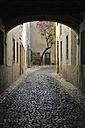 Portugal, Lisbon, Small cobblestone road through arch - RUE001136