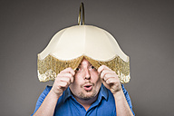 Portrait of mid adult man with electric lamp, close up - CA000024
