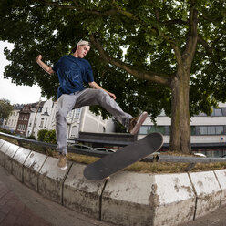 Germany, North Rhine Westphalia, Moenchengladbach, Young man skating on public place - KJ000251