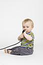 Portrait of baby boy holding electric plug - MUF001355