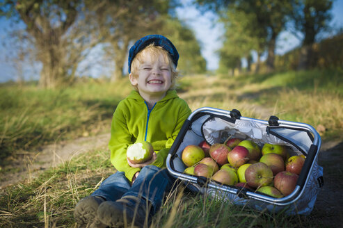 Germany, Saxony, Boy sitting with basket full of apples, smiling - MJF000316