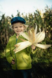 Germany, Saxony, Boy holding corn cob, smiling - MJF000313