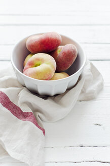 Peaches in bowl on wooden table with napkin - CZF000012