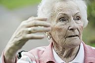 Germany, North Rhine Westphalia, Cologne, Senior woman sitting on wheelchair, looking away - JAT000219