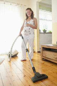 Germany, Brandenburg, young pregnant woman with vacuum cleaner - BFRF000262