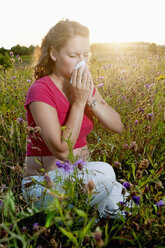 Germany, Brandenburg, young pregnant woman with hay fever kneeling in a flower meadow - BFRF000276