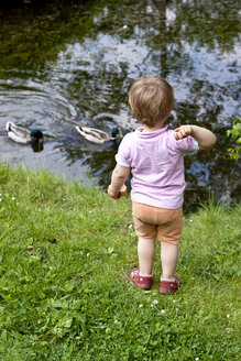 Germany, Kiel, girl stands at a pond feeding ducks - JFEF000170