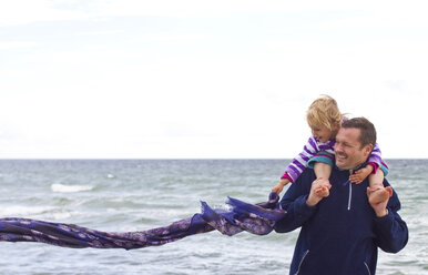 Danmark, Ringkoebing, little girl with her father on the beach, scarf flying - JFEF000189