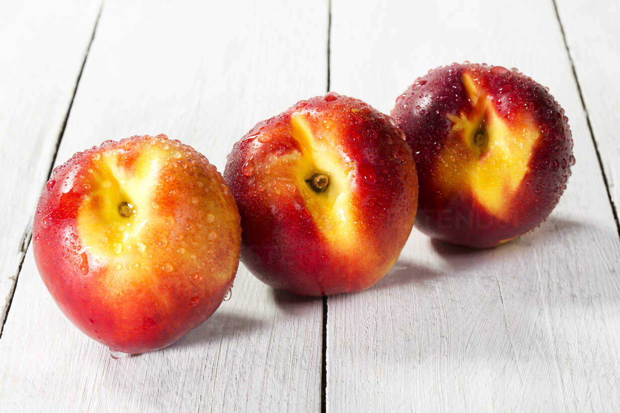 Nectarines on wooden table, close up - MAEF007197 - Roman Märzinger/Westend61