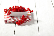 Bowl of currants on wooden table, close up - MAEF007198