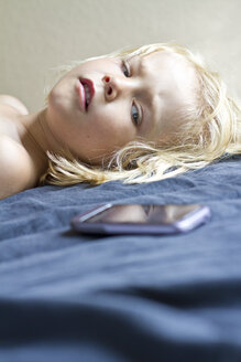 Germany, Kiel, Girl lying on bed with smart phone, close up - JFEF000184