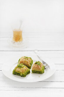 Plate of turkish baklava and glass of tea on wooden table, close up - CZF000036