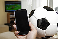 Mature man holding mobile with soccer ball and TV in background - KRP000027