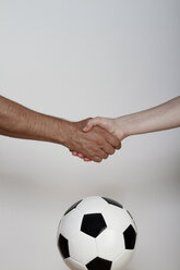 Man and woman shaking hands over soccer ball, close up - KRPF000024