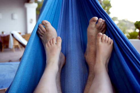 Spain, Mid adult man and boy legs relaxing on hammock - TKF000156