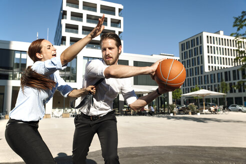 Businessman and businesswoman playing basketball outdoors - SU000023