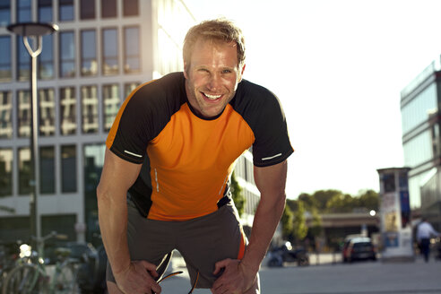 Smiling athletic man outdoors - SUF000041