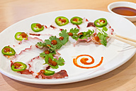 Plate of Japansese sashimi slices garnished with coriander and jalapenos - ABAF000992