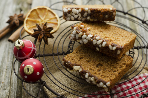 Gingerbread cake with christmas baubles and dried orange, spice on wooden table, close up - OD000321