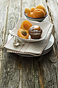 Bowls of apricot with muffin and chocolate on wooden table, close up - OD000315