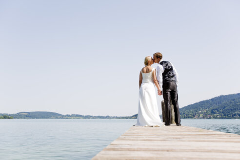 Germany, Bavaria, Tegernsee, Wedding couple standing on jetty - RFF000087