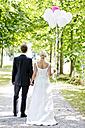 Germany, Bavaria, Tegernsee, Wedding couple walking under trees, holding balloons - RFF000102