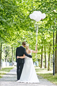 Germany, Bavaria, Tegernsee, Wedding couple walking under trees, holding balloons - RFF000103