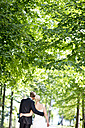 Germany, Bavaria, Tegernsee, Wedding couple walking under trees - RFF000104