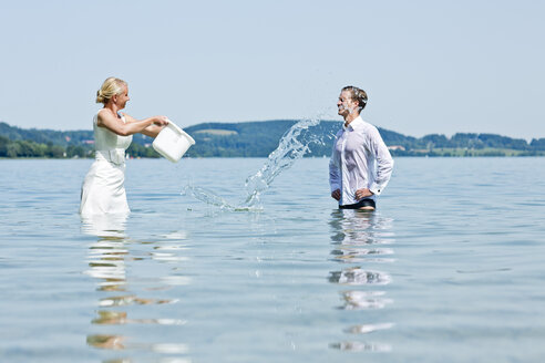 Germany, Bavaria, Tegernsee, Wedding couple standing in lake, pouring water over groom - RFF000100