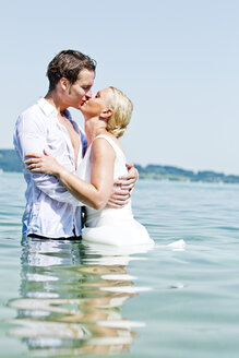 Germany, Bavaria, Tegernsee, Wedding couple standing in lake, kissing - RFF000108