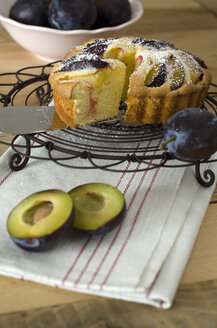 Bowl of prunes with prune cake on wooden table, close up - OD000330