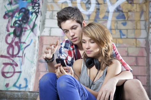 Germany, Berlin, Teenage couple on mobile phone - MVC000005